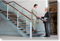 Zwei Geschäftsleute treffen sich im Treppenhaus